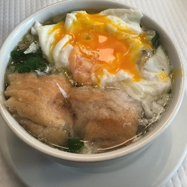 Simple galic and water broth with olive oil, poached egg, cilantro, and bread. Once the egg is broken and mixed with the soup, the broth becomes creamy, not filled with chunks of cooked yolk, as you might expect.