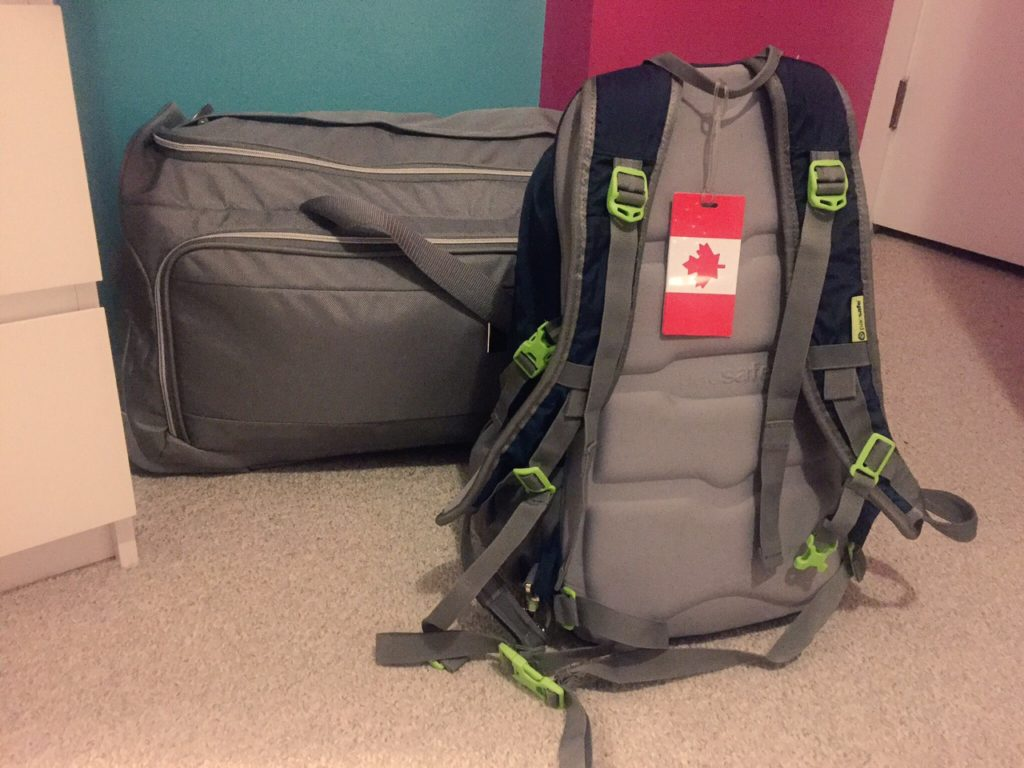 I always check a large duffle bag and wear a carry-on 30L backpack, plus a messenger bag for my essential documents and a book or two.
