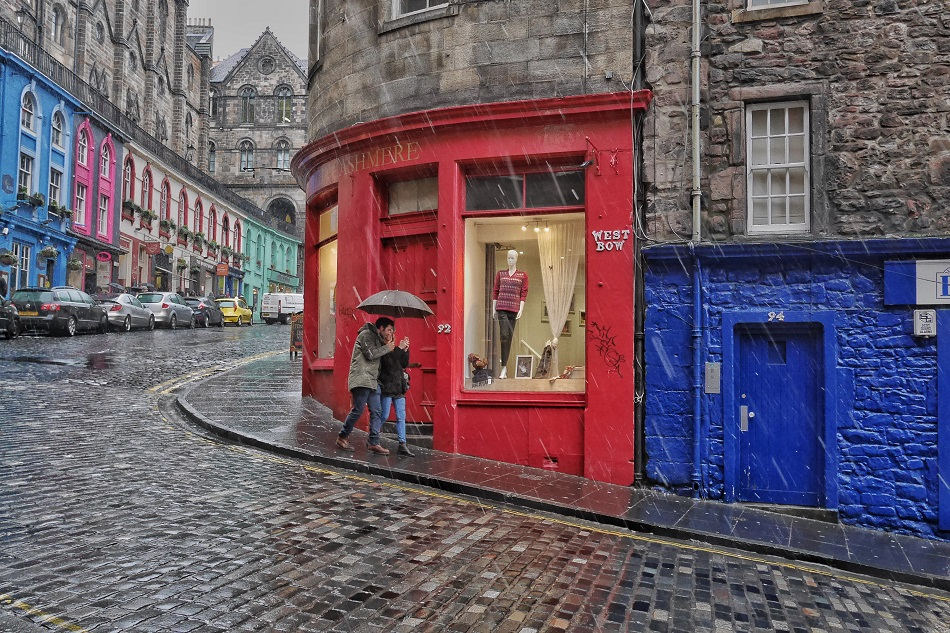 A couple huddles under their umbrella on Victoria/Bow Street in Edinburgh.